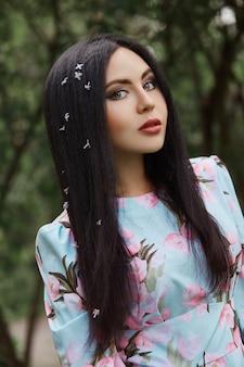 Brunetki kobieta w gałąź piękny kwiatonośny drzewo.