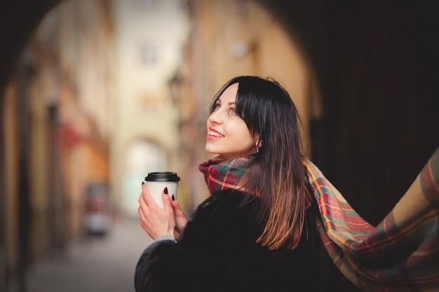 Brunetki kobieta z filiżanką kawy w starym miasteczku