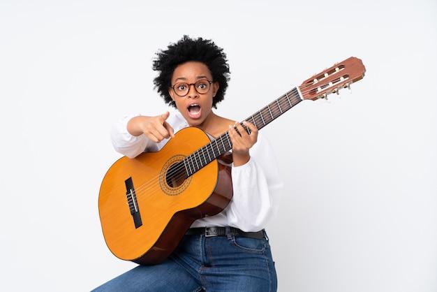 Brunetki kobieta z gitarą nad białym tłem