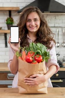 Brunetki kobieta z papierową torbą pełno zdrowy jedzenie