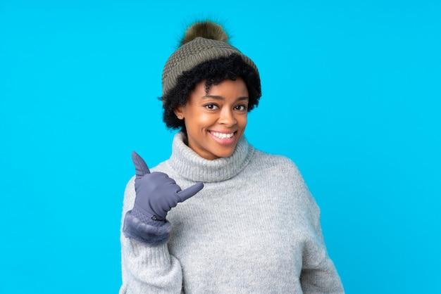 Brunetki kobieta z zima kapeluszem nad odosobnionym błękitnym tłem