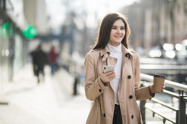 Brunetki kobiety model pije kawę wśrodku dużego centrum handlowego
