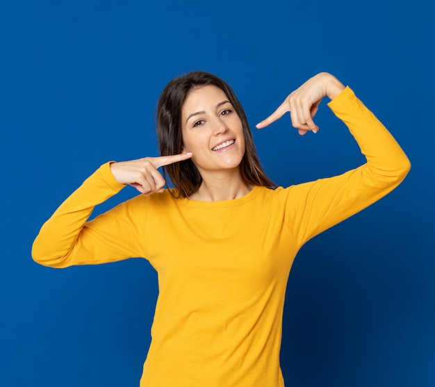 Brunetki młoda kobieta gestykuluje nad błękit ścianą