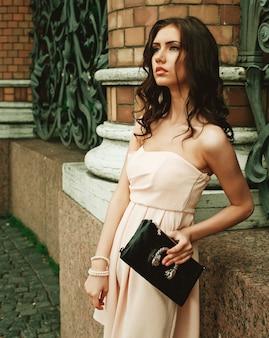 Brunetki młoda kobieta jest ubranym suknię