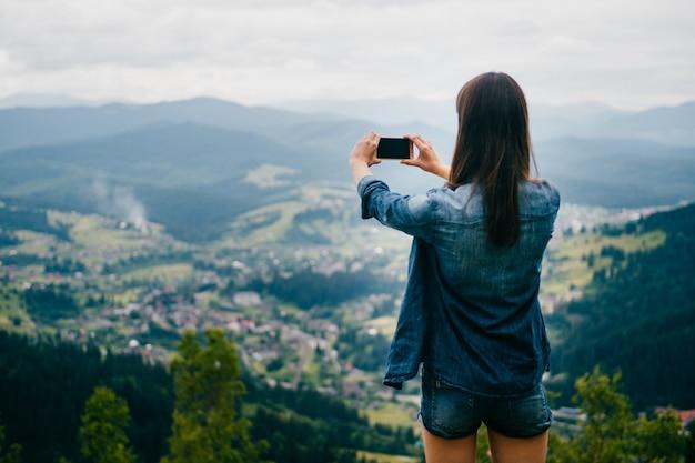 Brunetki nastoletnia dziewczyna pozuje na górze góry w lecie i bierze fotografię z smartphone