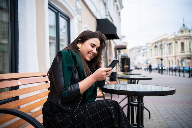 Brunetki piękna elegancka caucasian kobieta w przypadkowym stroju na europejskiego miasta ulicznym obsiadaniu przy cukiernianą pisać na maszynie wiadomością na jej telefonie.