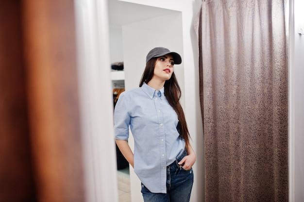 Brunetki wspaniała dziewczyna w butiku sklepu odzieżowego przy przypadkowymi ubraniami i nakrętką przeciw lustrem.