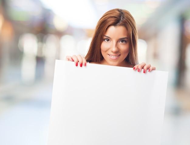 Brunette kobieta trzyma biały znak