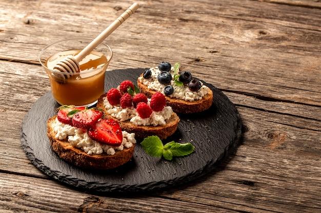 Bruschetta lub tosty z kozim serem, jagodami i miodem. tło przepis żywności. zamknij widok z góry