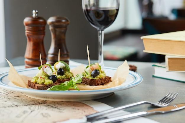 Bruschetta na drewnianym stole w białym talerzu i kieliszek czerwonego wina