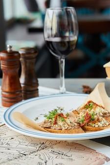 Bruschetta na drewnianym stole w białym talerzu i kieliszek wina