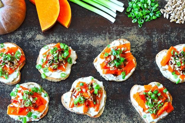Bruschetta z dynią. tosty z pieczoną dynią, zieleniną i białym serem. zdrowe przekąski otwarte kanapki z dynią.