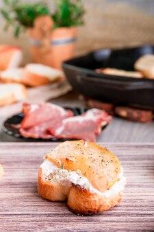 Bruschetta z kremowym serem i gruszką na drewnianym.