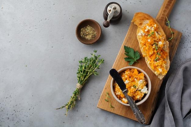 Bruschetta z pieczoną dynią, serem feta i tymiankiem na szarym kamieniu lub betonowej powierzchni
