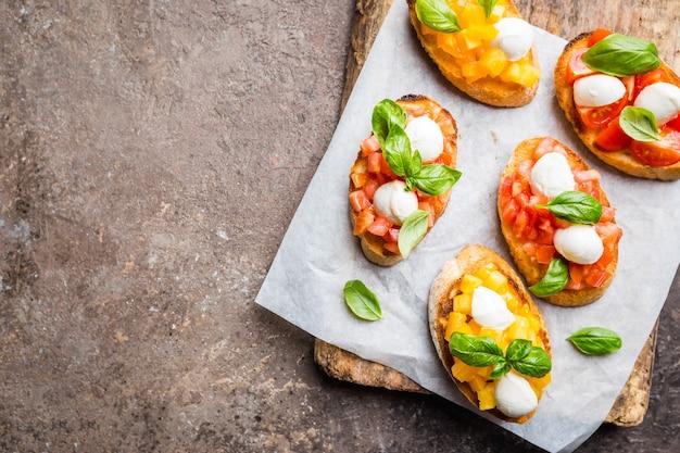 Bruschetta z pomidorami, bazylią i mozzarellą na desce
