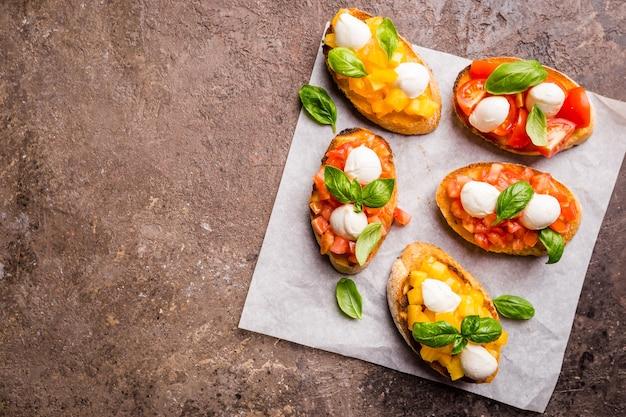 Bruschetta z pomidorami, bazylią i serem mozzarella na drewnianej desce widok z góry. tradycyjna włoska przystawka lub przekąska, antipasto