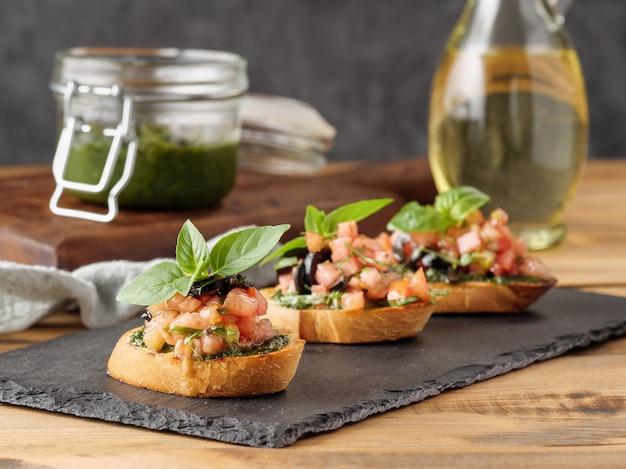 Bruschetta z pomidorami i pesto na drewnianym stole. skopiuj miejsce.