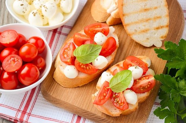Bruschetta z pomidorami koktajlowymi i mozzarellą na drewnianej desce do krojenia