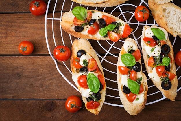 Bruschetta z pomidorami, mozzarellą, oliwkami i pesto bazyliowym