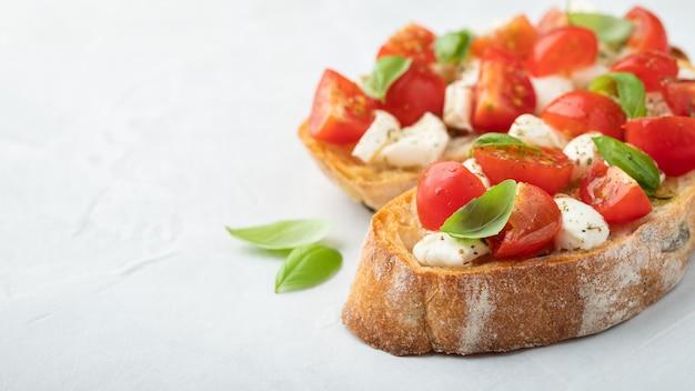 Bruschetta z pomidorami, serem mozzarella i bazylią.