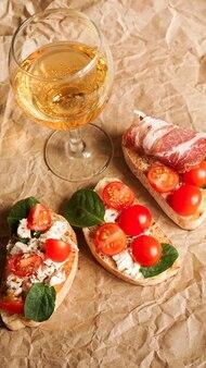 Bruschetta z pomidorkami koktajlowymi. kieliszek do wina, włoska przystawka. tło papieru rzemiosła. koncepcja piknikowa