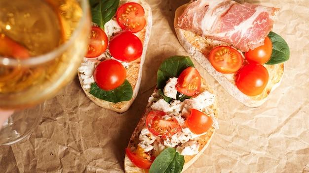Bruschetta z pomidorkami koktajlowymi. kieliszek do wina, włoska przystawka. tło papieru rzemiosła. zestaw trzech bruschettów. koncepcja piknikowa