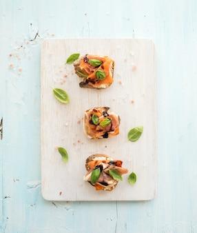 Bruschetta z prosciutto, pieczonym melonem, miękkim serem i bazylią na drewnianej desce do serwowania na jasnoniebieskim stole