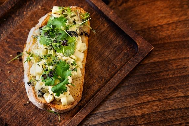 Bruschetta z serem i zieleniną na drewnianej desce do krojenia do zdjęć i kręcenia filmów. pracuje jako stylista żywności i fotograf. menu restauracji i kafe