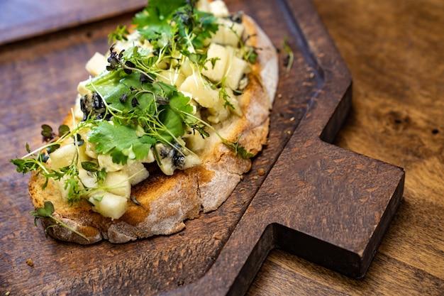 Bruschetta z serem i zieleniną na drewnianej desce do krojenia do zdjęć i kręcenia filmów.