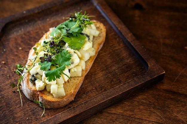 Bruschetta z serem i zieleniną na drewnianej desce do krojenia do zdjęć