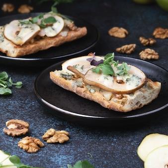 Bruschetta z serem pleśniowym gorgonzola, gruszkami i orzechami włoskimi na ciemnych talerzach na ciemnej powierzchni. apetyczna bruschetta. kuchnia śródziemnomorska.
