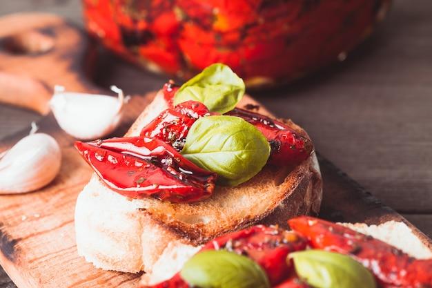 Bruschetta z suszonymi pomidorami, listkami bazylii i czosnkiem