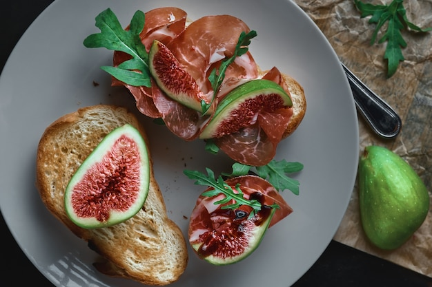 Bruschetta z szynką prosciutto, serem ricotta, rukolą i świeżymi figami na talerzu.
