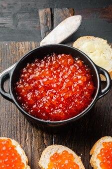 Bruschettes z czerwonym kawiorem masła, na starym ciemnym drewnianym stole w tle