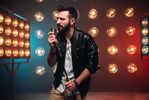 Brutalna, brodata piosenkarka z mikrofonem na scenie