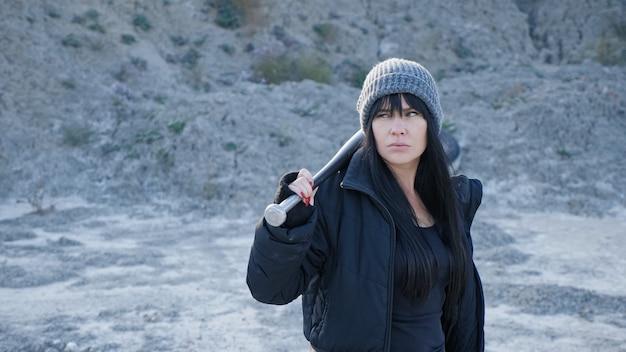Brutalna kobieta z gangów chuliganów idzie na pustkowiu z kijem baseballowym.