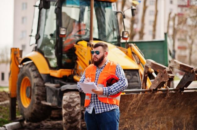 Brutalny broda pracownik człowiek garnitur robotnik budowlany w bezpieczeństwo kask pomarańczowy, okulary przeciw traktor z planem papieru pod ręką.