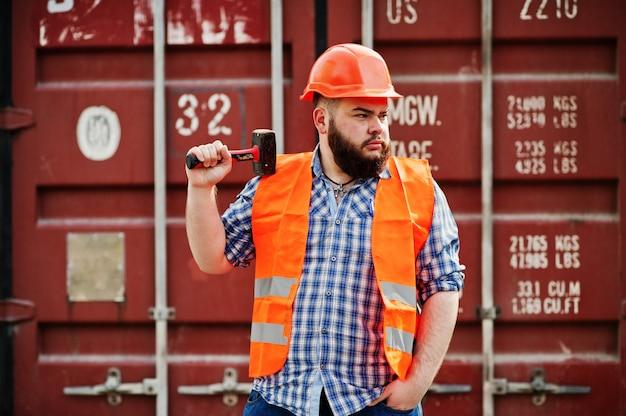 Brutalny broda pracownik człowiek garnitur robotnik budowlany w bezpieczeństwo pomarańczowy kask z młotem na rękę.