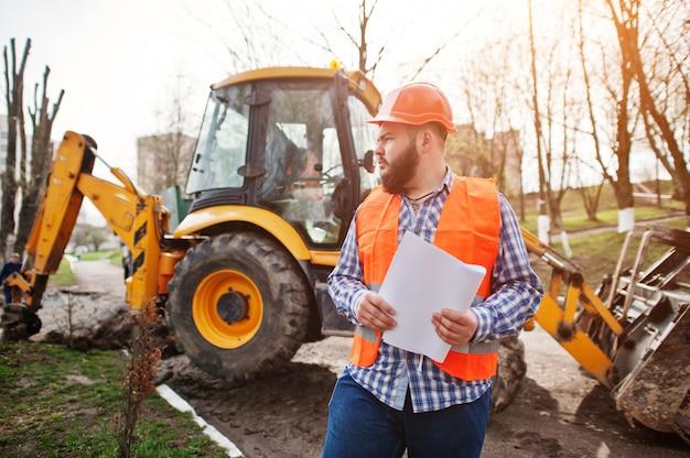Brutalny broda pracownika mężczyzna kostiumu pracownik budowlany w pomarańczowym hełmie przeciw traktorowi z planem tapetuje przy rękami.