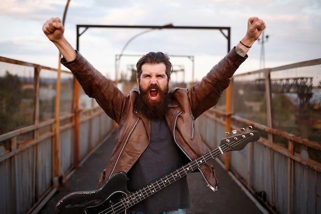 Brutalny brodacz gitarzysta z wąsami w brązowej skórzanej kurtce podniósł ręce i krzyczy na gitarze