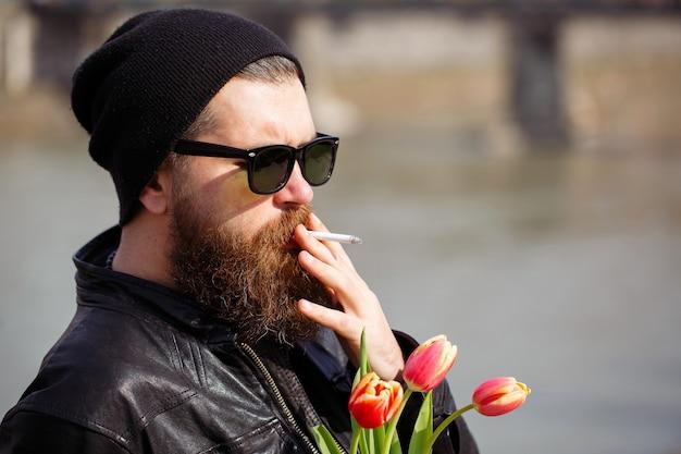 Brutalny brodacz w okularach przeciwsłonecznych z wąsami w ciepłej czapce i skórzanej kurtce z bukietem czerwonych tulipanów pali papierosa