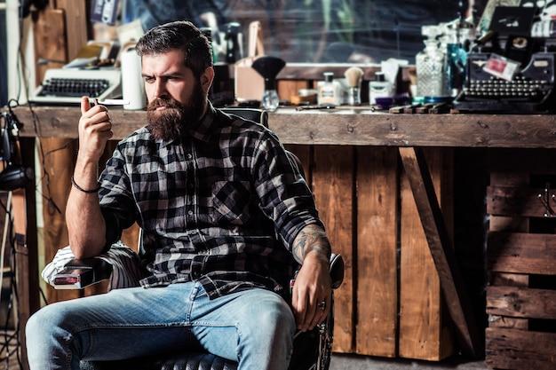Brutalny brodaty facet siedzi w fotelu fryzjerskim. zakład fryzjerski vintage, golenie. brodaty styl, moda.