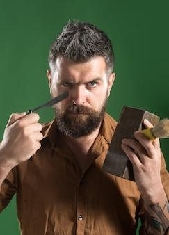 Brutalny brodaty kaukaski hipster z długą brodą z brodą i wąsami trzyma w rękach