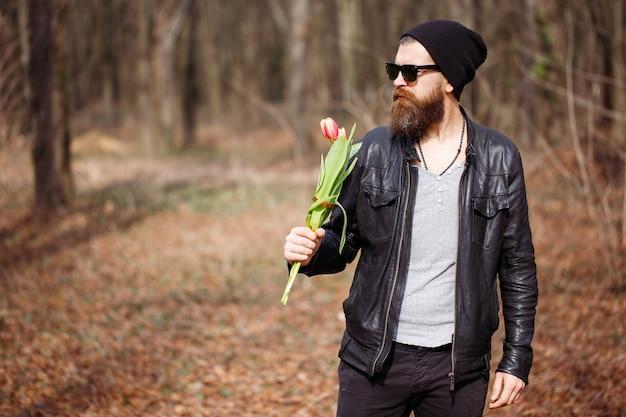 Brutalny, brodaty mężczyzna macho w czarnej skórzanej kurtce z siwymi włosami w ciepłej czapce i ciemnych okularach przeciwsłonecznych trzyma bukiet czerwonych tulipanów