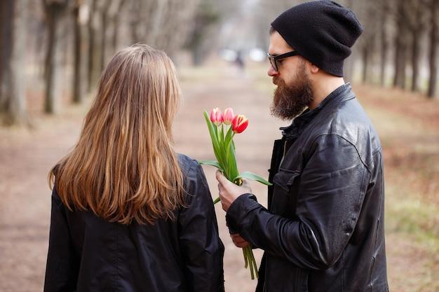 Brutalny, brodaty mężczyzna macho w okularach, skórzanej kurtce i ciepłej czapce daje bukiet czerwonych tulipanów dziewczynie z długimi włosami na ulicy w parku