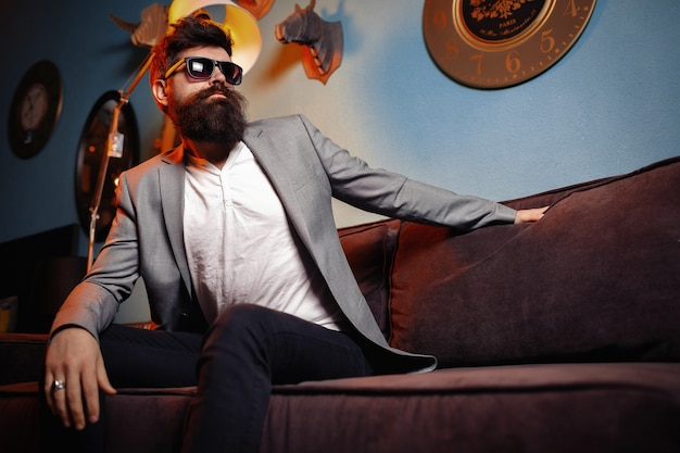 Brutalny brodaty mężczyzna siedzi w wygodnej kanapie. przystojny, brodaty mężczyzna w garniturze na luksusowej kanapie.