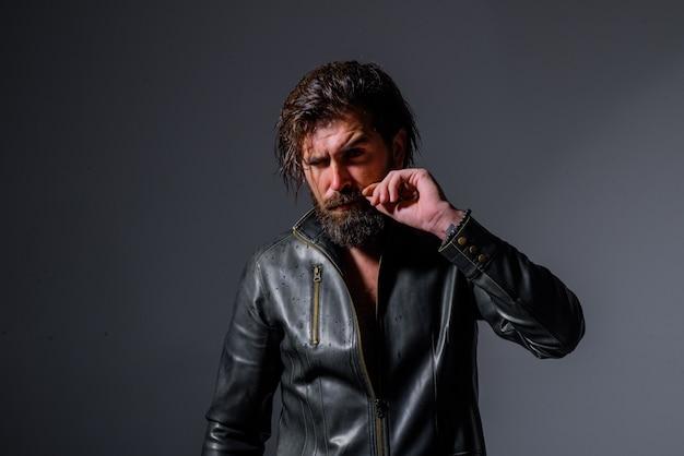 Brutalny brodaty rowerzysta przystojny mężczyzna w skórzanej kurtce fryzjer sklep modne ubrania brodaty mężczyzna