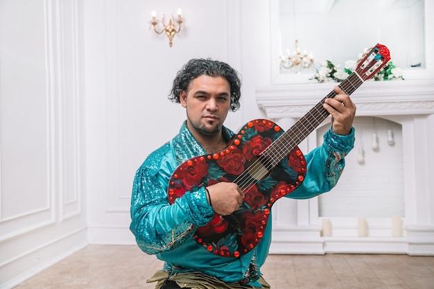 Brutalny cygan z gitarą śpiewający piosenkę. zdjęcie z miejscem na kopię