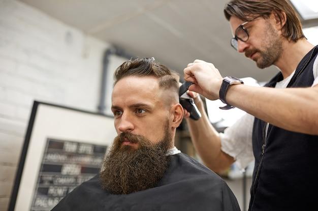 Brutalny facet w nowoczesnym barber shop. fryzjer robi fryzurę mężczyźnie z brodą. portret stylowy mężczyzna broda.