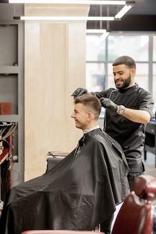 Brutalny facet w nowoczesnym sklepie fryzjerskim. fryzjer sprawia, że fryzura jest mężczyzną. mistrz fryzjer robi fryzurę maszynką do strzyżenia włosów. fryzjer